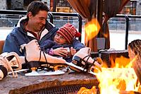 A father and daughter relaxing next to a fire at an ice skating rink at Northstar ski resort near Lake Tahoe in California