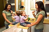 A mother and her baby daughter in their bathroom at home, both brushing their teeth