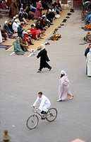 Prayer time and cyclist, Djeema-el- Fna square , Marrakesh, Morocco, Africa