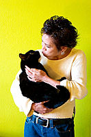 Contemporary looking Asian woman affectionately holding a black cat