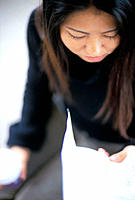 Woman looking over a letter while holding a coffee