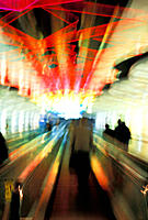 Blurred view of people using a horizontal escalator with neon lights in international airport