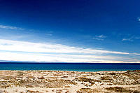 Issyk-Kul Lake, (Ysyk-köl)  in Kyrgyzstan, Central Asia, seen from southern beach, west of Bökönbaev, with dry lands around with xerophytes and snowcl...