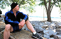 Man, 40-45, with winter cap, sitting on rock after jogging, looking out to the Potomac River