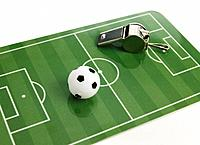 Little soccer ball and whistle on green cutting board