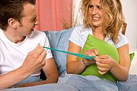 Teenage boy and girl fooling around with condom