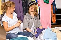 Two teenage girls trying on clothes