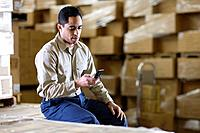 Man Using Cell Phone in Warehouse