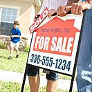 Parents Standing by Sold Sign for House (thumbnail)