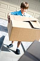 Boy Carrying Cardboard Box While Moving