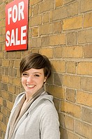 Young woman and for sale sign