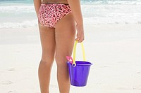 Rear view of a girl holding a bucket and spade