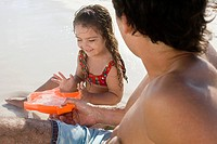 A father and daughter playing on a beach