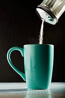 Pouring sugar into a coffee cup