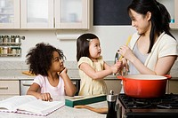 Children helping a woman cook