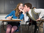 Boy whispering to girl in class