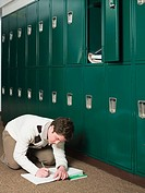Boy writing by lockers