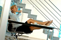 Young businesswoman relaxing on office chair
