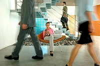 Businesswoman sitting on chair with laptop while colleagues walking on floor