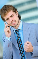 Businessman conversing on mobile phone, close_up