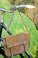 Old leather bag hanging on bicycle handlebar