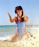 Woman in swimsuit playing with sand