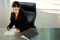 Businesswoman sitting at a desk and signing documents