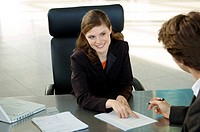 Businesswoman pointing at a contract and businessman sitting in front of her