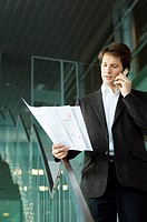 Businessman talking on a mobile phone and looking at a blueprint