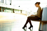 Side profile of a businesswoman using a laptop at an airport lounge