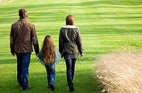 Rear view of a girl walking with her parents in a park