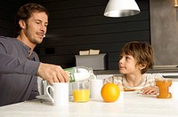 Mid adult man having breakfast with his son in the kitchen (thumbnail)