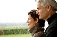 Mature man and a mid adult woman looking out through a window (thumbnail)