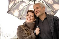 Close_up of a mid adult woman and a mature man under an umbrella