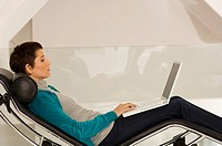 Businesswoman reclining on a chaise longue and using a laptop