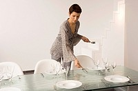 Mid adult woman setting a dining table