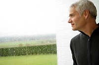 Close_up of a mature man looking out through a window