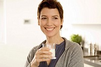 Mid adult woman holding a glass of milk