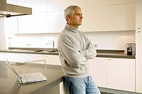 Mature man leaning against a kitchen counter