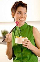 Close_up of a mid adult woman eating food with chopsticks