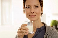 Close_up of a mid adult woman holding a glass of milk