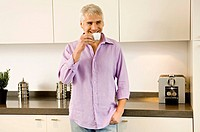 Mature man drinking tea in the kitchen