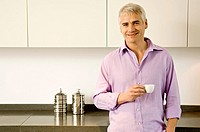 Portrait of a mature man holding a cup of tea and smiling