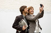 Young woman taking a picture with a digital camera and a mid adult man standing behind her