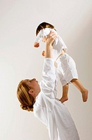 Side profile of a young woman lifting up her son (thumbnail)