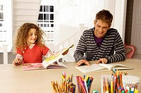 Mid adult man sitting with his daughter and reading books (thumbnail)