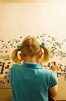 Rear view of a girl playing a jigsaw puzzle