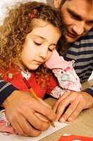 Mid adult man helping his daughter in drawing
