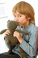 Portrait of a boy kissing a teddy bear