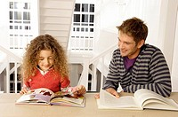 Mid adult man sitting with his daughter and reading books